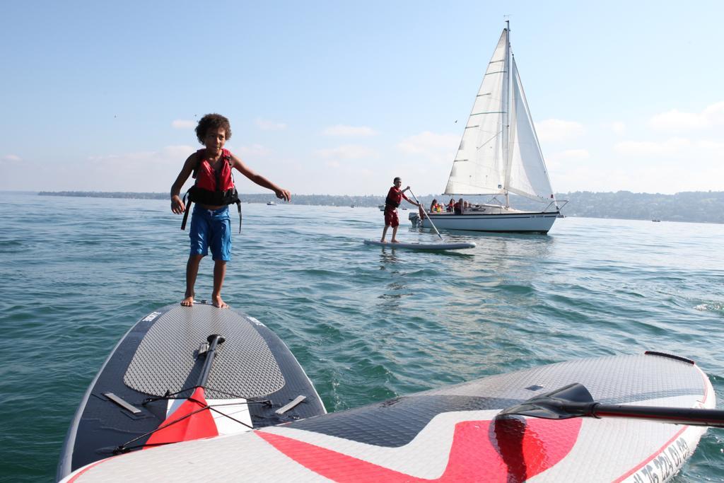 Un enfant joue sur une planche, au loin, un voilier prend le large
